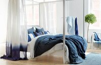 Four-poster bed with blue and white linen and curtains