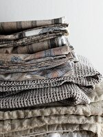 Sand-coloured and grey bed linen and blankets