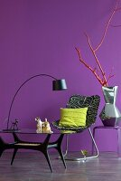Arc lamp on glass table, printed easy chair and silver-glazed ceramic vase on side table against purple wall