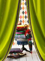 Colourful arrangement of accessories seen through green curtains