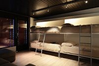 Four beds folded down from wall in multifunctional room