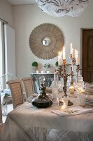 Candelabra on festively set dining table in front of antique mirror on wall