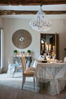 Chandelier with net cover above candles on festively set dining table in front of antique mirror on wall