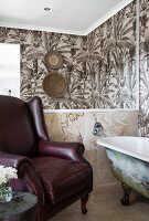 Free-standing bathtub, leather armchair, mirror and wallpaper with pattern of palm trees in bathroom