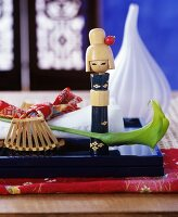 Japanese Kokeshi doll and green calla lily on black lacquered tray