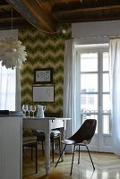 Chair and white dining table in front of retro wallpaper and French window in renovated period apartment