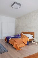 Rough wall and colourful blanket in simple bedroom