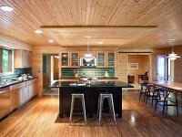 Black kitchen counter and bar stools in open-plan kitchen in bright, renovated wooden house