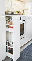 A pull-out shelf in a white kitchen unit