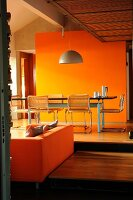 Dining table in front of orange wall on raised platform