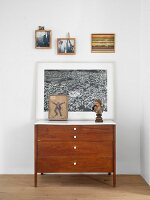 Artwork on top of vintage chest of drawer in bedroom