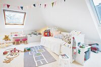 A white bed with colourful cushions and a hopscotch rug in a light and bright young girl's bedroom with slanted roof