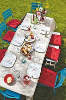A table set with a paper tablecloth and a menus in a garden