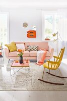 A living room with a pale pink sofa, a tray table and a yellow rocking chair