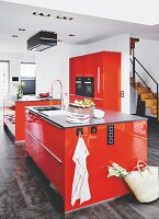 Two red islands and a red cupboard with fitted appliances in a kitchen