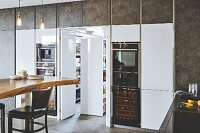 A kitchen with white glossy cupboards and a hidden adjoining room