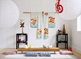 Japanese sitting room with a white panelled wall, hanging kimono, paper lanterns, black lacquered side tables, and a low wooden table with floor cushions.