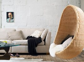 Ecru couch with scatter cushions and comfortable, wicker hanging chair with fur blanket