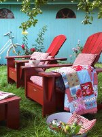 Patterned cushions and blankets on red wooden armchairs in garden