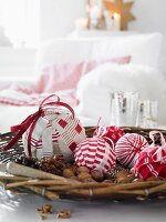 Red and white fabic Christmas baubles and nuts in a bowl