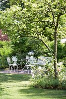 Bistro furniture in seating area in shade of wild cherry in garden