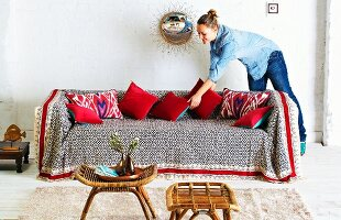 Woman arranging scatter cushions on sofa with colourful throw