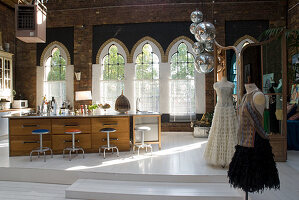Large, free-standing kitchen island and tailor's dummies wearing elegant gowns in brick loft with church windows