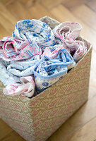 Nostalgic country house patterns in pale blue and pink - rolled bed linen in box covered with pattern of dog roses