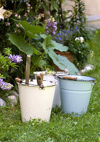Vintage-style metal buckets in front of flower bed