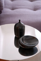 Black-glazed ceramic vessels on reflective metal top of side table; detail of sofa in background