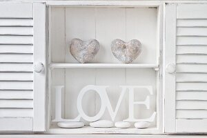 Cabinet holding white-painted wooden letters and stone heart sculptures