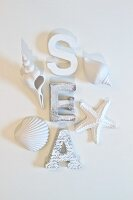 White-painted wooden letters and seashells