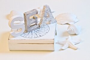 White-painted wooden letters on box surrounding by seashells