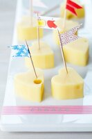 Heart-shaped pieces of cheese with toothpick flags made using masking tape