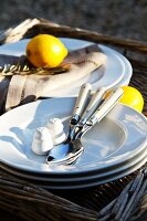 Lemons, plates and cutlery on wicker tray