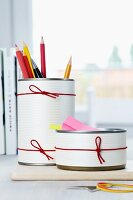 Pencil holders made from tin cans decorated with paper and rubber bands