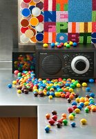 Radio and multicoloured sweets on stainless steel worksurface against tapestry with fields of different colours