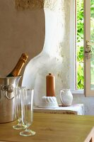 Bottle of sparkling wine and wineglasses on wooden table in front of earthenware pots in niche
