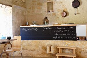 Raised kitchen island within ancient sandstone walls of Chateau Maignaut