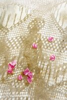 Rose petals on sand and pattern of light and shade through crocheted hammock