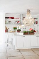 White, open-plan kitchen with magnificent chandelier above island counter