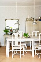 White dining table, chairs and pendant lamps