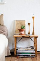 Houseplant, candlesticks and drawing on wooden bedside table in bedroom with wooden floor
