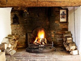 Open fire flanked by stacked firewood in inglenook fireplace