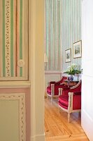 View through open door of Baroque armchairs with red, satin upholstery against striped wallpaper