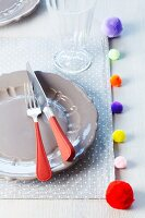 Place mat decorated with colourful pompoms