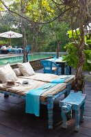Sun loungers with cushions and animal-shaped stool on terrace in front of large pool of water in tropical garden