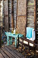 Spa toiletries on bench in front of wooden panels alternately filled with sticks and rattan