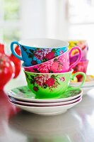 Stacked, rose-patterned teacups in bold colours