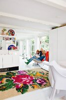 Family in white, open-plan interior with large-format rose pattern on kilim rug